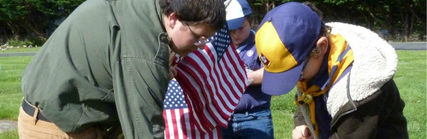 Scouts placing flags on graves