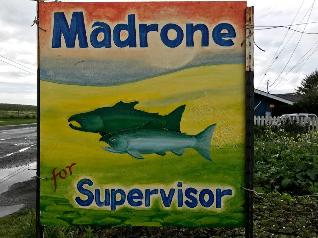 Salmon decorate this sign supporting Madrone.