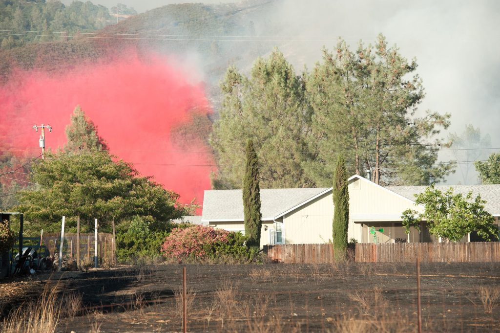 A tanker dropped retardant to protect a home. [
