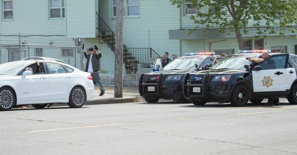 Officers have their guns drawn and are focused on the white vehicle occupied by the suspects. [Crop of a photo by Mark McKenna]