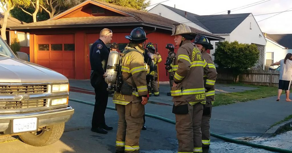 Firefighters standing in front of the duplex that caught fire.