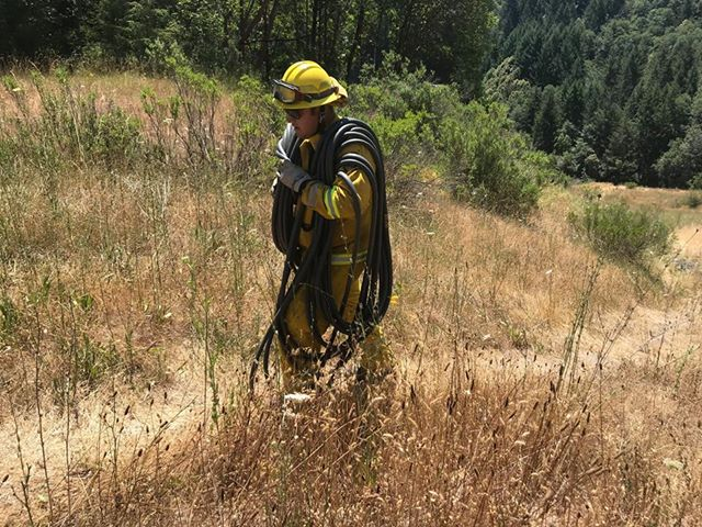 Firefighter hiking with line looped over his shoulders.