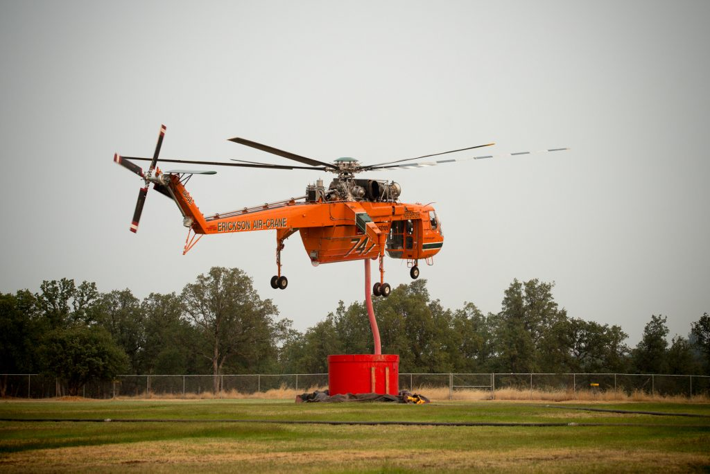 A Sikorsky helicopter fills up with fire retardant from tanks on the field of Igo, Ono, Platina Elementary School south Redding.