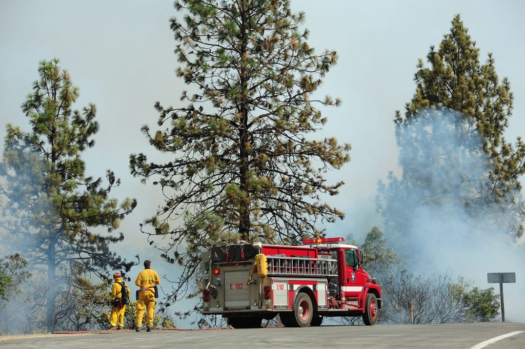 Fire fighters prepare to fight flames as they climb up a hill near Whiskey Town Lake in Shasta County.