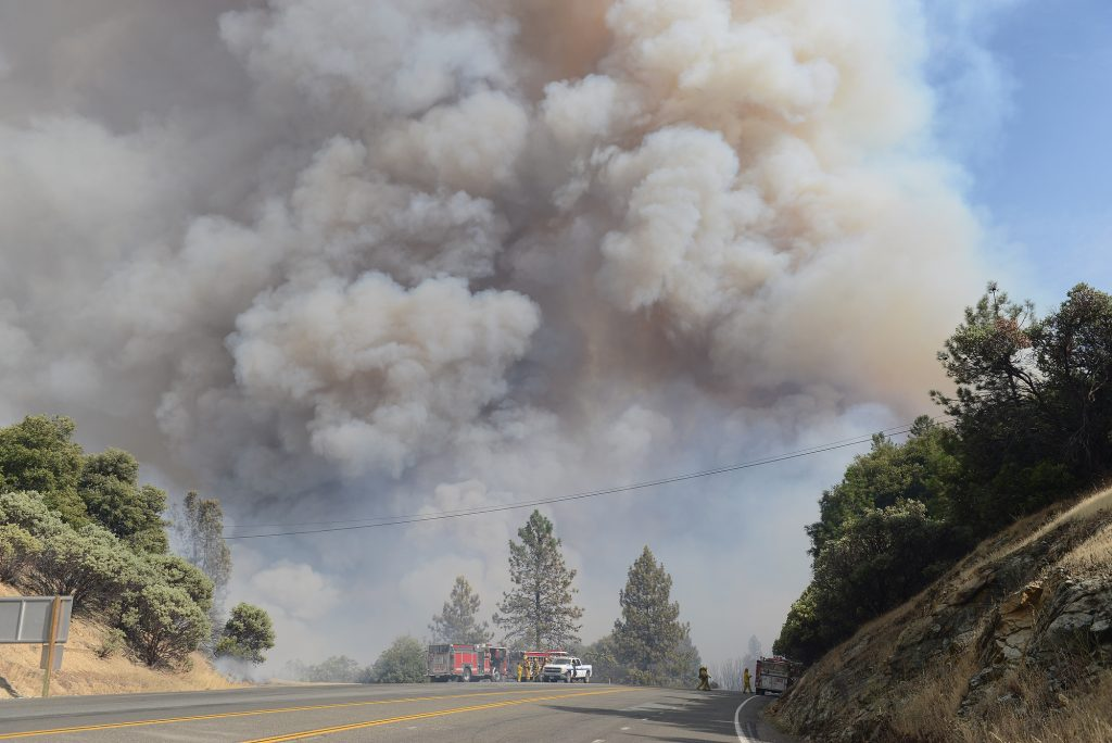 A large column of smoke approaches fire fighters near Whiskeytown Lake.