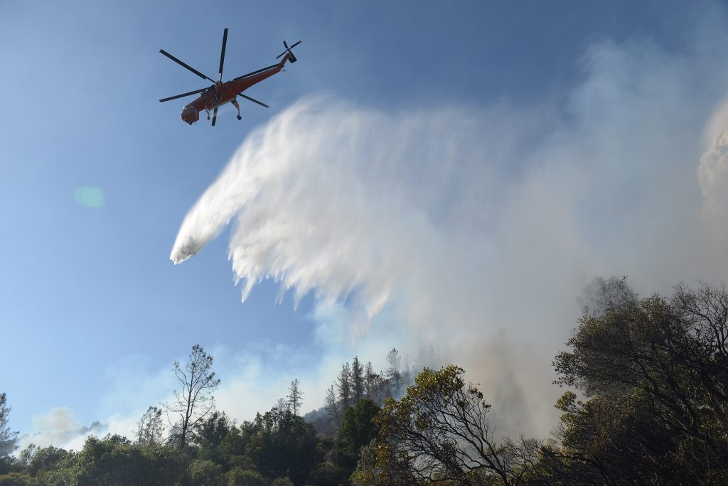 A Sikorsky helicopter drops water on a hot spot near the lake.