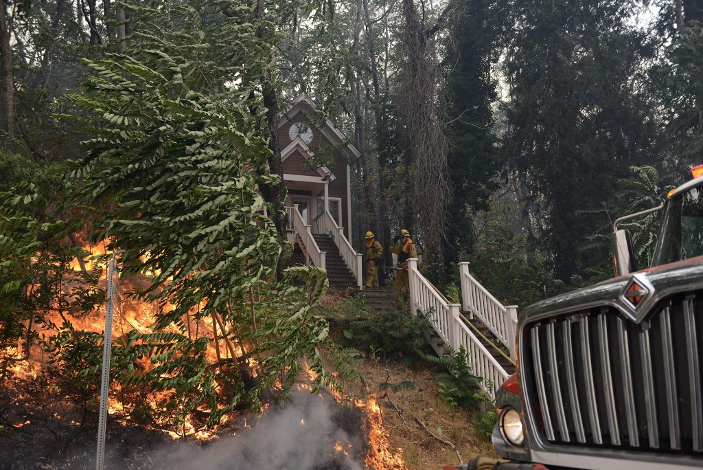 A crew from Mendocino County tries to save a house in the city of Shasta, California.