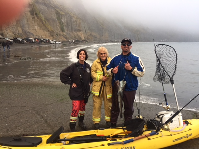 Cheryl Antony in her turnouts flanked by the fisherman and the Shelter Cove Fire medic Shelly Mendes.