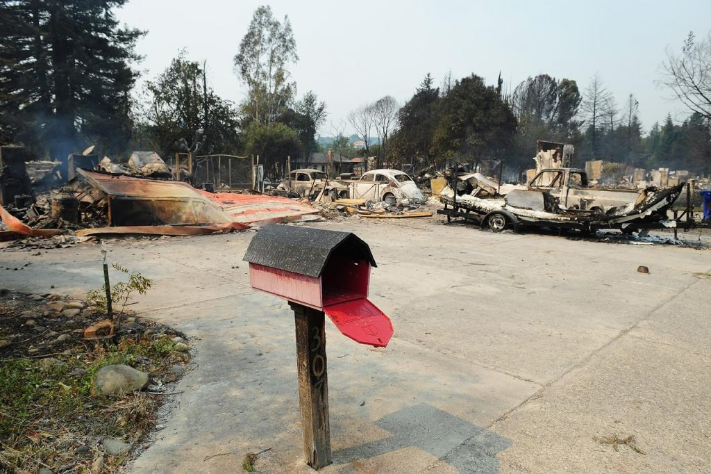 A mailbox gapes open in front of devastation Carr Fire