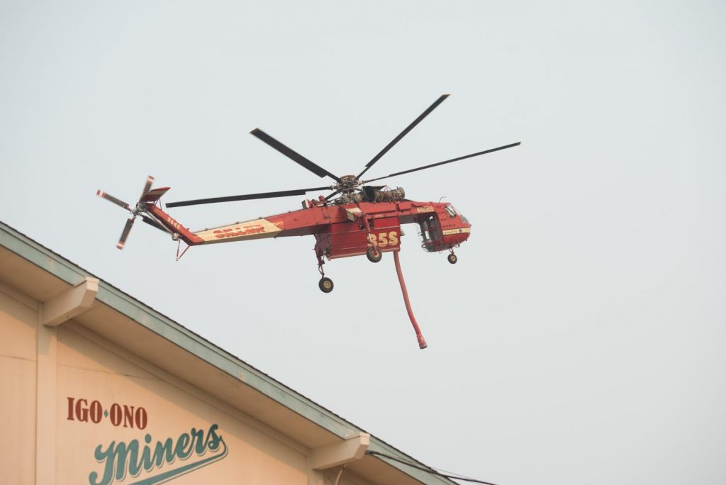 A Sikorsky helicopter prepares to fill up with fire retardant from tanks on the field of Igo, Ono, Platina Elementary School south Redding.