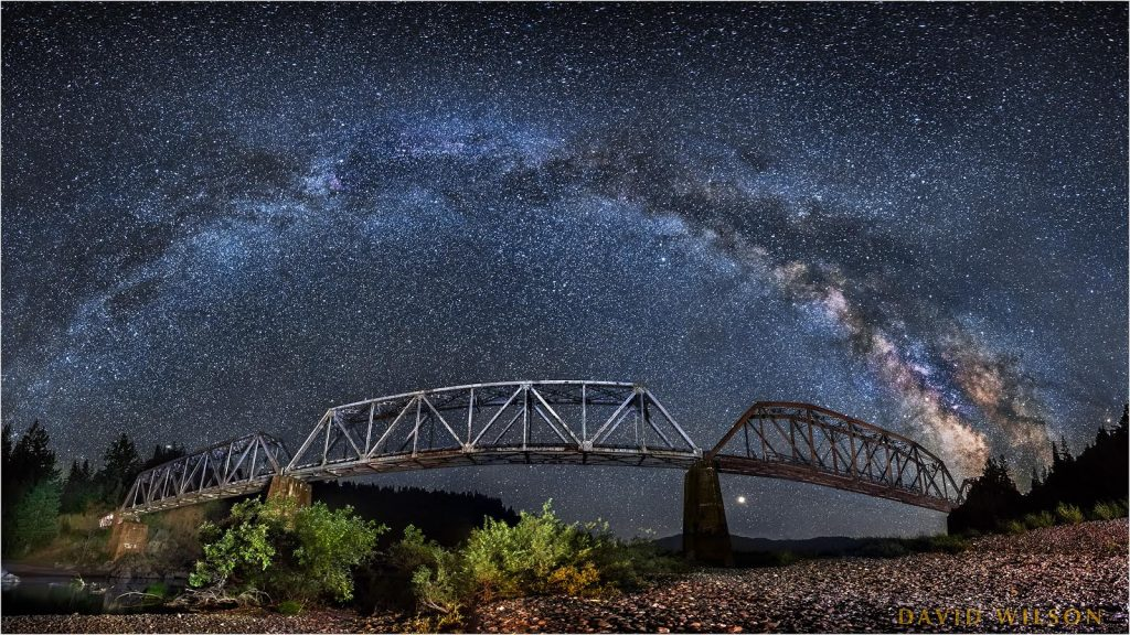 The South Fork Bridge, or Dyerville Train Trestle, of the Northwestern Pacific Railroad, crosses the North Fork Eel River beneath the Milky Way, just north of the confluence with the South Fork Eel River. Humboldt County, California. [Image by David Wilson]