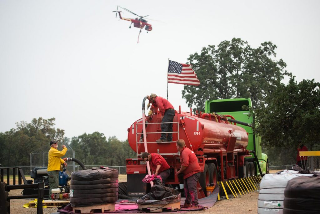 Crews work to mix fire retardant for helicopter battling the car fire near the town of Igo.