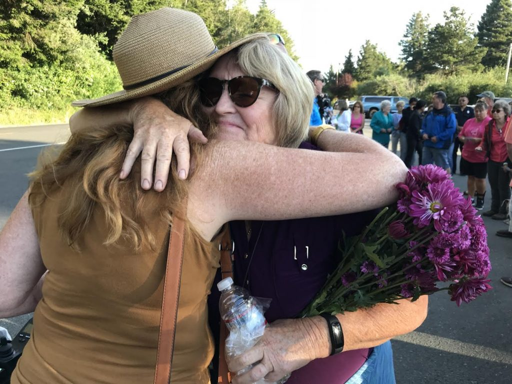 A family friend of the Tsarnas family, Sharron Grover, holding a bouquet of flowers hugs another attendee at the event. hug