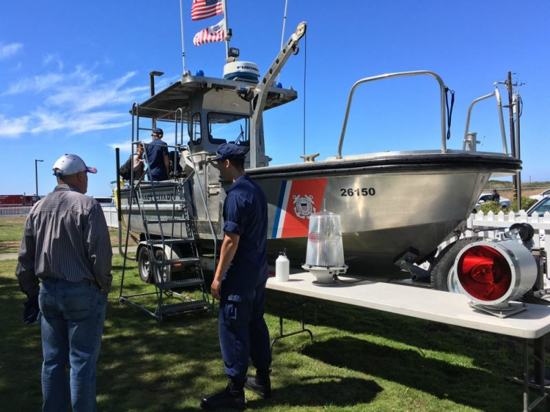 A Coast Guard Station Humboldt Bay crew member talks about Coast Guard assets with a local citizen at the station's annual open house event in Samoa, Calif., Aug. 11, 2018. Coast Guard members spoke with attendees about the Coast Guard's many missions in the area, provided general boating safety tips and demonstrated how the Coast Guard helps mariners operating off in the region.