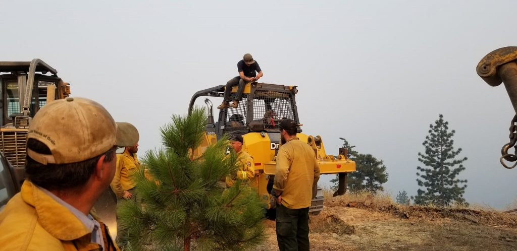 Silas Paula on top of his family's heavy equipment as the crews plan their routes.