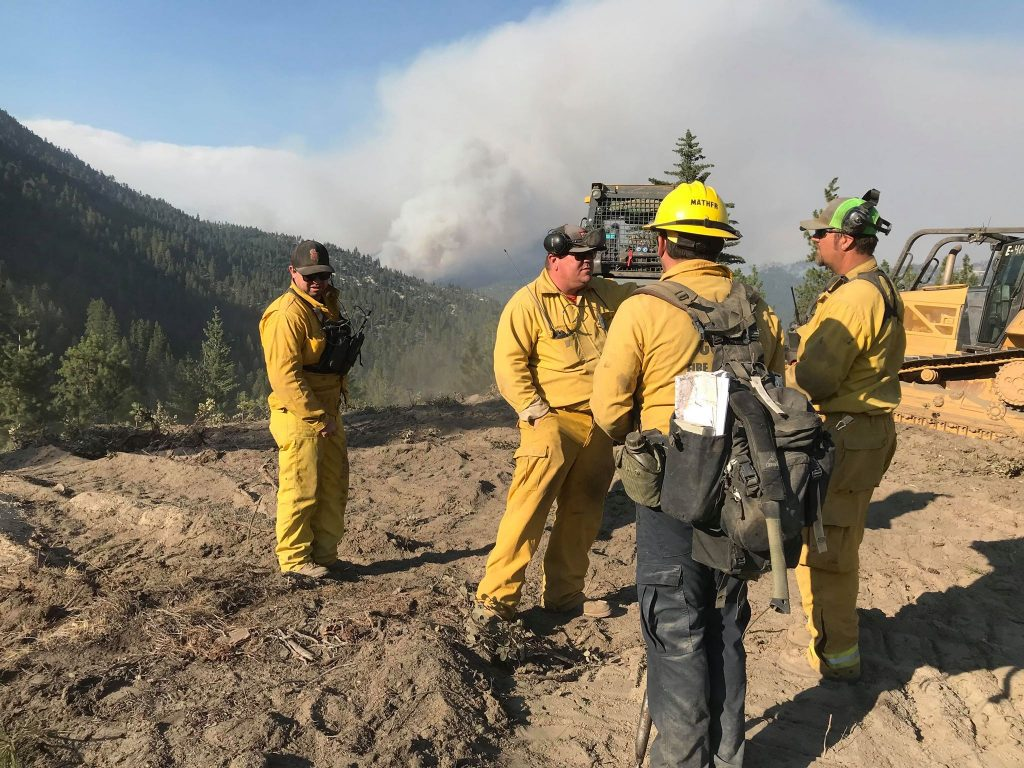 Crews consult about where to put in containment lines.