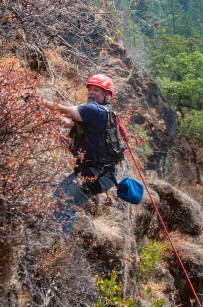 One of the team members from the EVRTR climbs down a steep cliff while securely anchored by ropes from both sides.