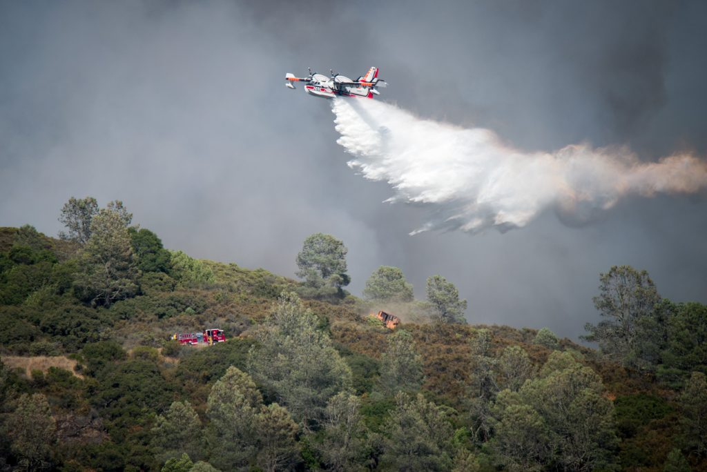 A Aero-Flite Inc.CL-215-6B11 plane under contract with Cal Fire drops water on a hill above the town of Lucerne in Lake County California.