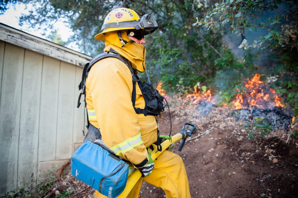 Palo Alto firefighter Manny Macias monitors the growth of a burn out being conducted near a home to help fight The River Fire on Scott's Valley Road in Lake County.