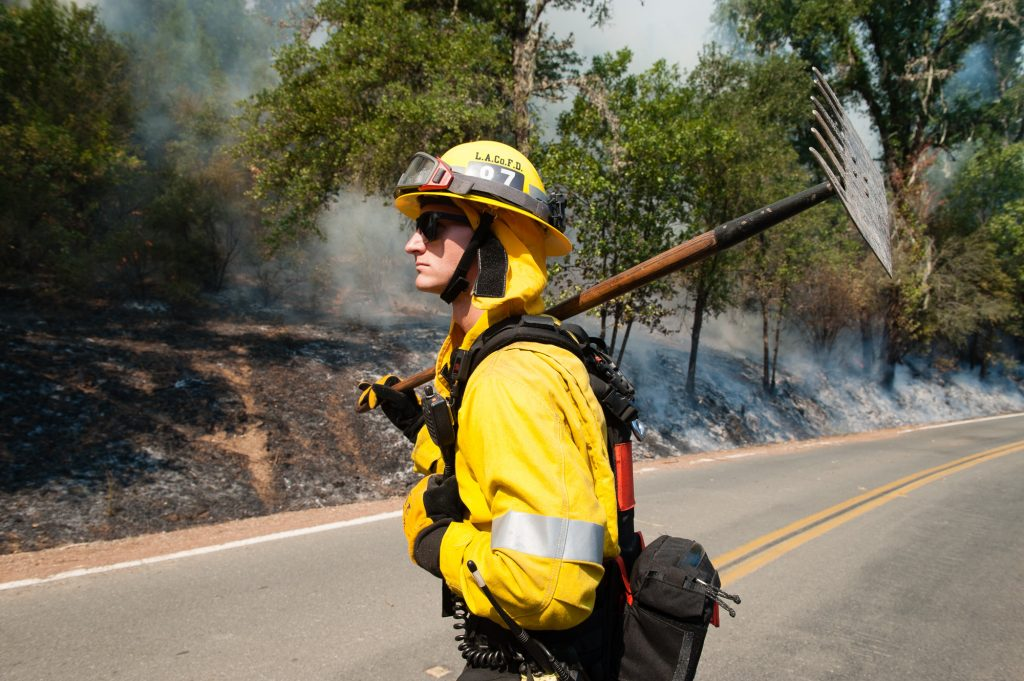 Los Angeles County Firefighter Zach Kling watches the progress of a burn out operation on Scott's Valley Road in Lake County California to stop the spread of the River Fire.