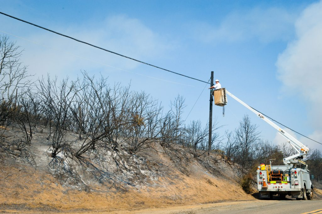 An Altec employee restrings line talked out by the River Fire on Hendricks Road near Lakeport.