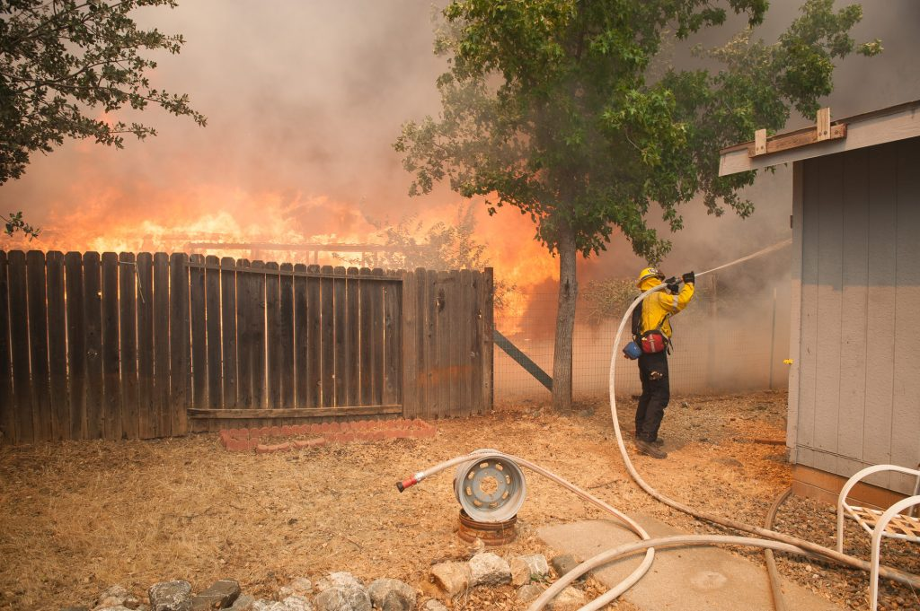 A firefighter from Beverly Hills sprays down a house next one burning in Spring Valley.