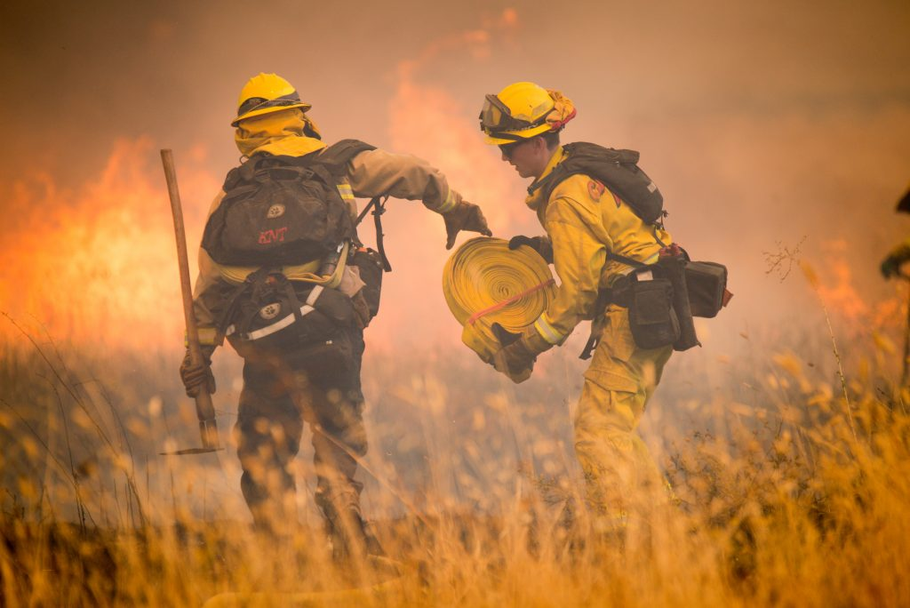 Firefighters with Cal Fire rush to add more hose to a line while fighting spot fires in a field in High Valley near the town of Clearlake Oaks from the Ranch Fire on Sunday.