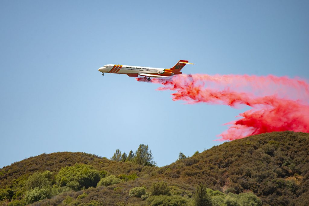 An MD87 Air Tanker drops fire retardant on a ridge West of Scotts Valley Road.