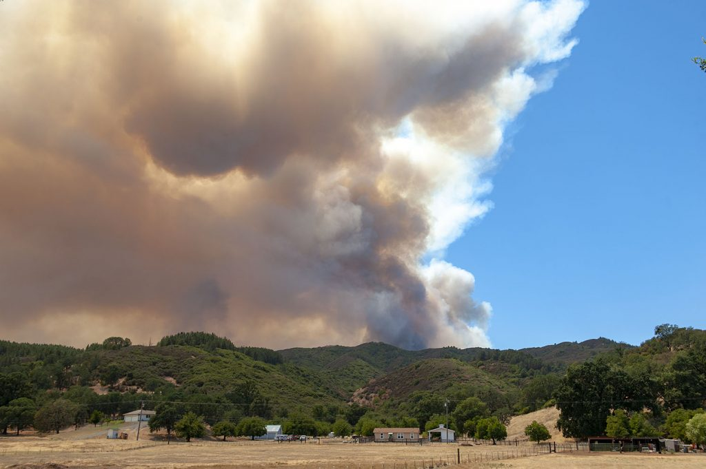 A large plume of smoke from the River Fire rises over house off Scotts Valley Road near Lakeport, California.
