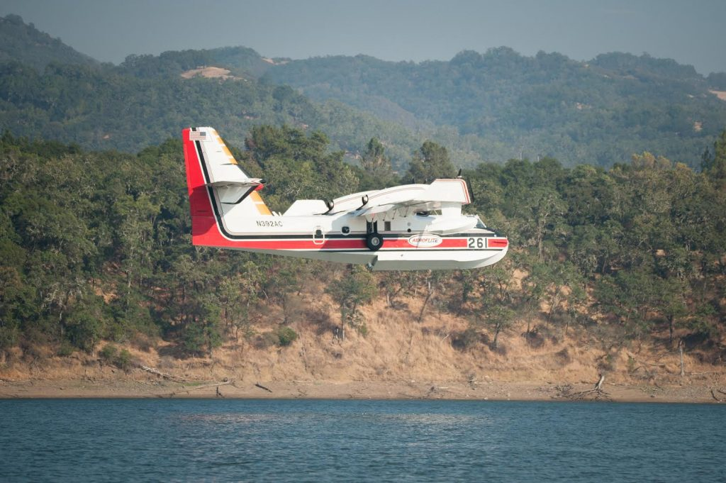 A Aero-Flite Inc.CL-215-6B11 plane under contract with Cal Fire approaches Lake Mendocino, where it will skim the surface of the lake to refill with water.
