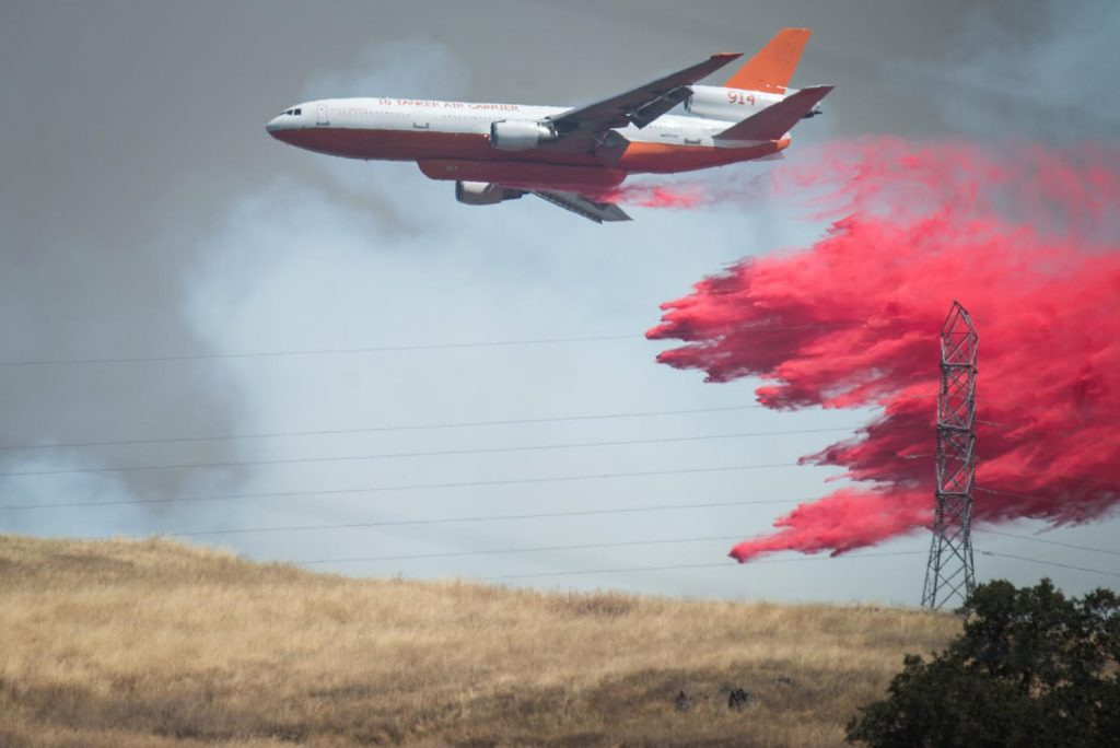 A DC-10 drops retardant on a hill a move the town of Lucerne to stop the spread of the rapidly expanding Ranch Fire Burning in Lake County California.