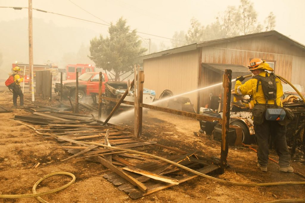 A firefighter hoses a burning fence next to a Spring Valley home in Lake County as the Ranch Fire continued to spread.