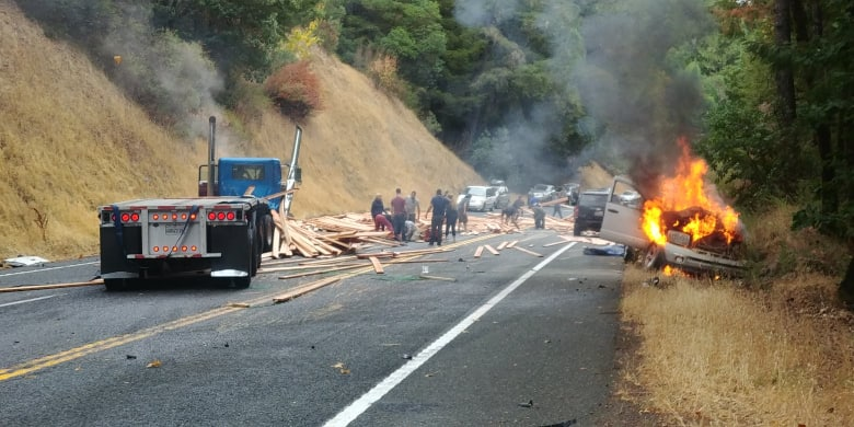 A vehicle burns as shocked onlookers attempt to remove lumber from the road.
