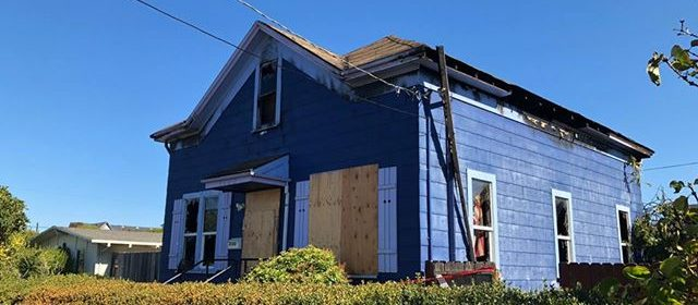 Boarded up windows and blackened eaves mark the home that caught on fire last night