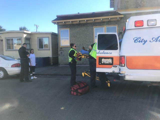 Emergency personnel load the injured woman onto the ambulance.