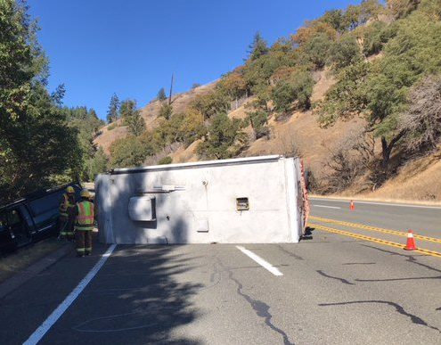 An overturned trailer is blocking both lanes.