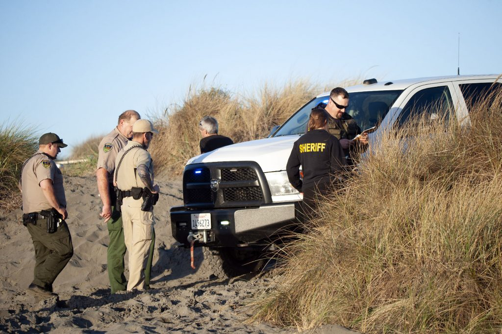 Humboldt County Sheriff's personnel gather near a vehicle parked in the dunes near the north spit.