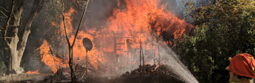 A firefighter keeps flames from spreading from the house