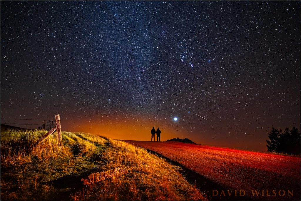 Silhouettes of David and son with Geminid meteor.