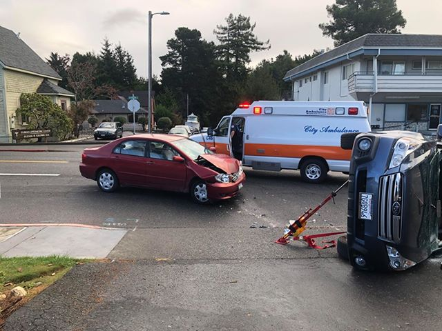 An ambulance waits by one vehicle.