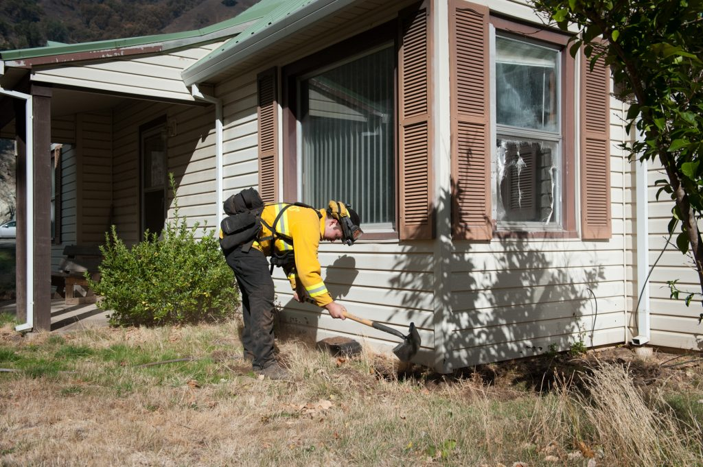 A firefighter out of Siskiyou County clears grass away from a home.
