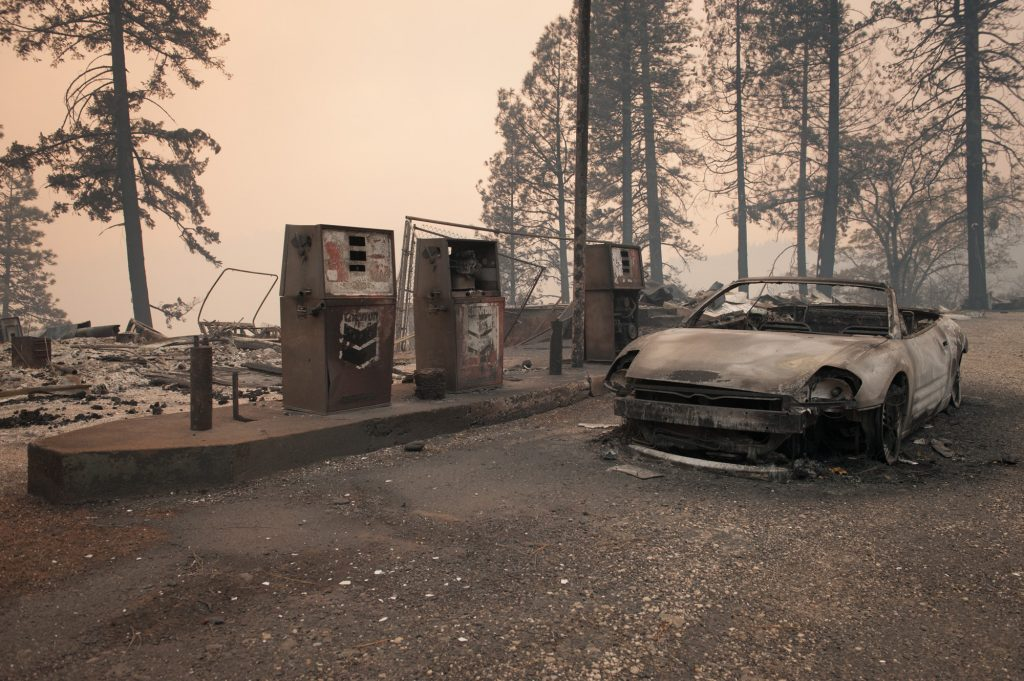 A burned car sits near gas pumps at a station on Highway 70.