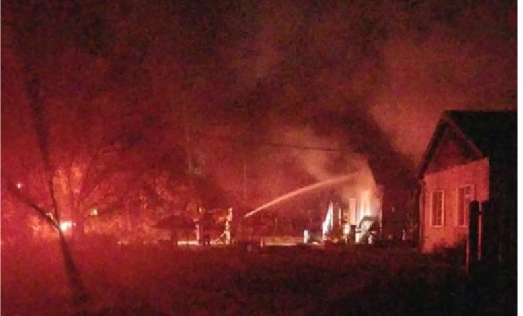 A firefighter directs a stream of water at the burning home.