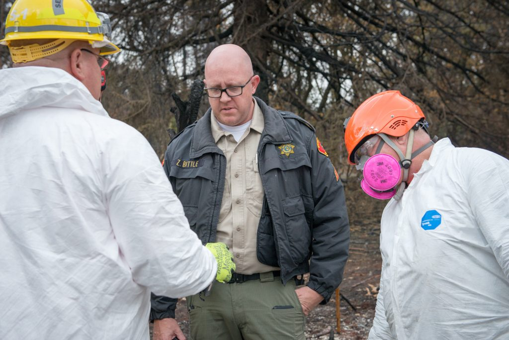 Sgt Zack Bittle looks at what a member of the Kern County Search and Rescue team thought might be bone fragment.
