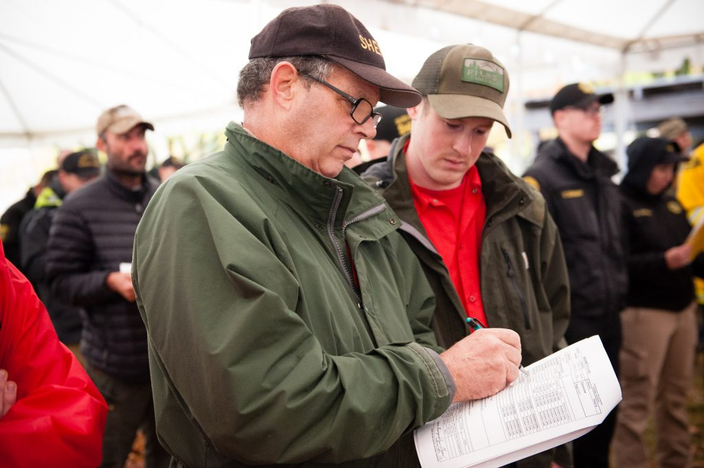 Team leader Mike Robertson and Logan Mitchell look and the Incident Action Plan during their first morning briefing on Thanksgiving Day.
