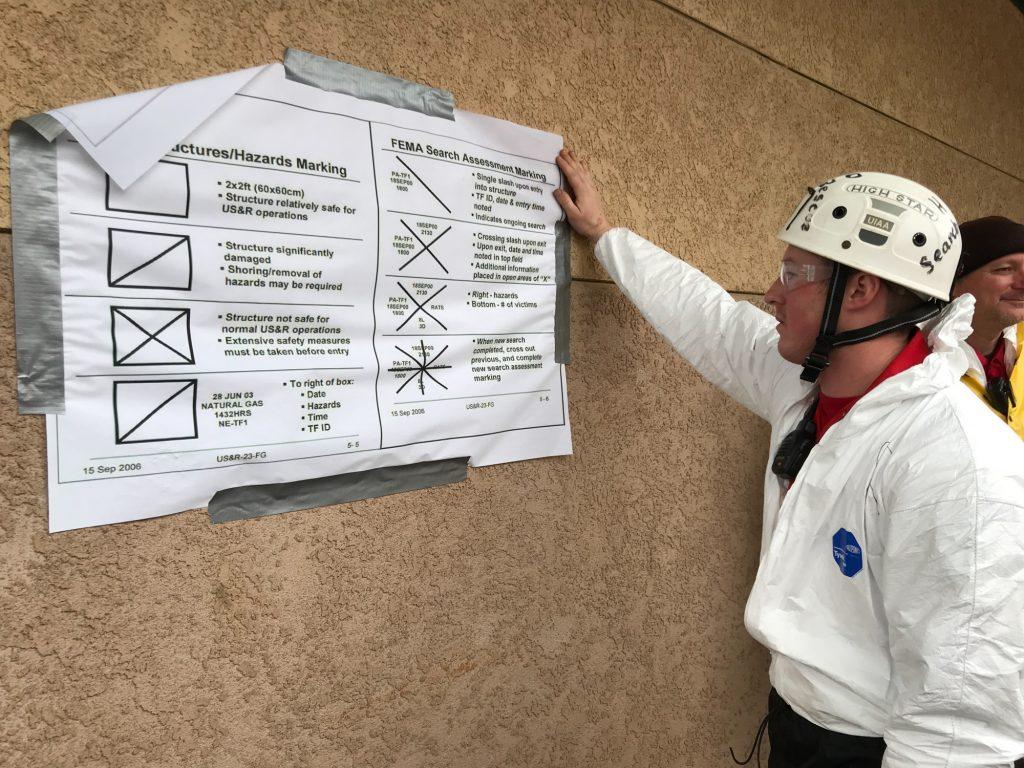 Logan Mitchel checks the diagram detailing the FEMA markings they will use.