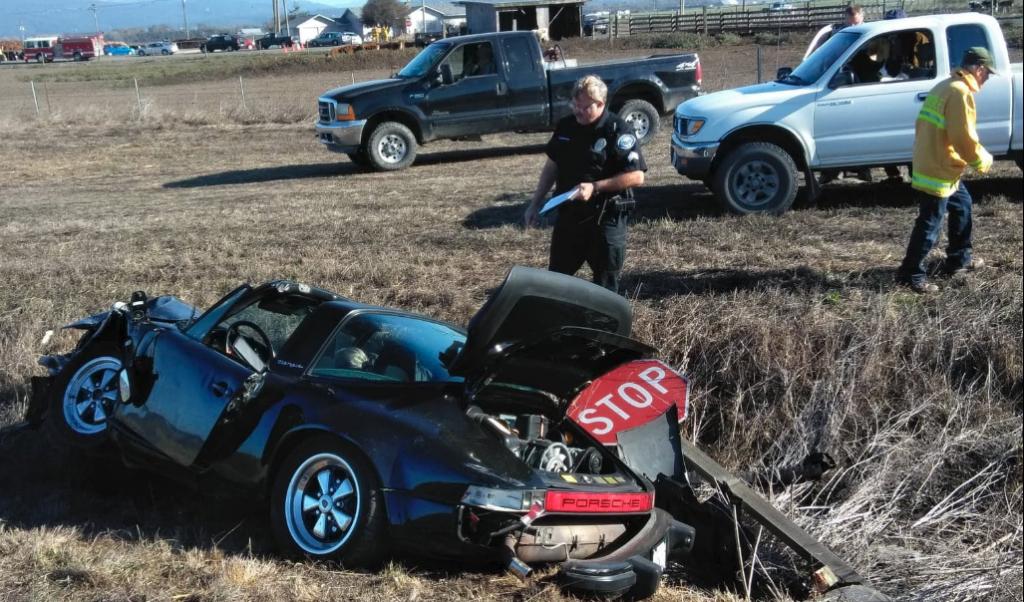 A stop sign leans against the damaged Porsche.