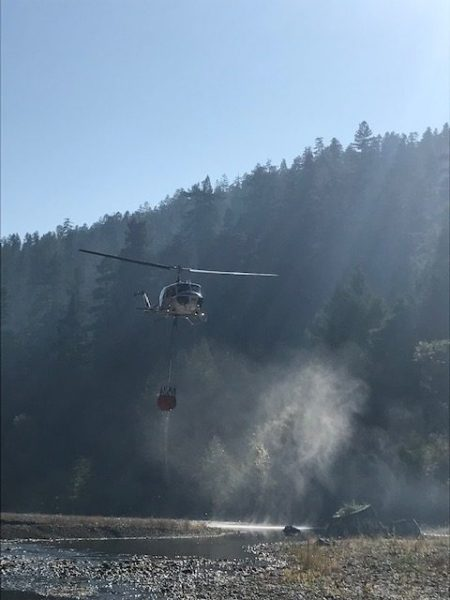 Cal FIre helicopter dipping for water from the extremely low for November Eel River. [