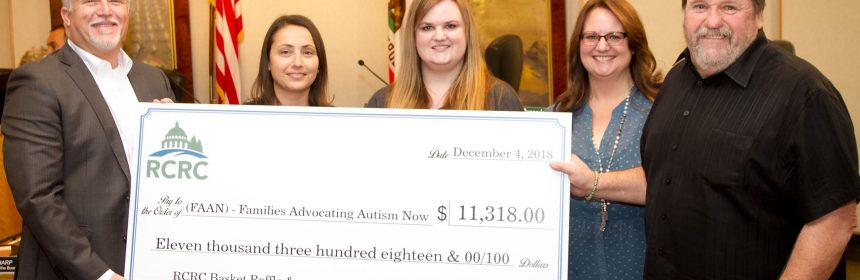 Members of FAAN (Families Advocating Autism Now) accepting a their share of the money raised.