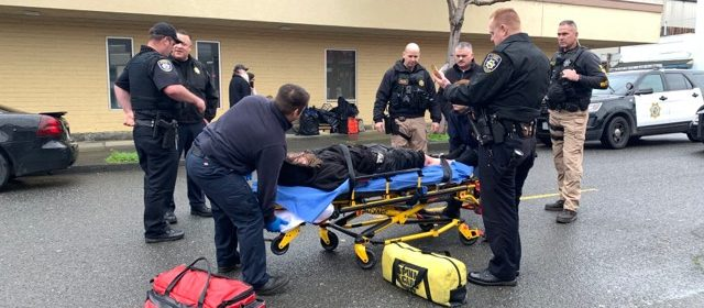 A stretcher arrives to pick up a handcuffed man surrounded by law enforcement.
